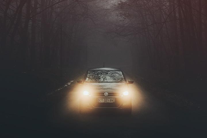 Vista frontal de carro trafegando em estrada ao anoitecer com luzes acesas
