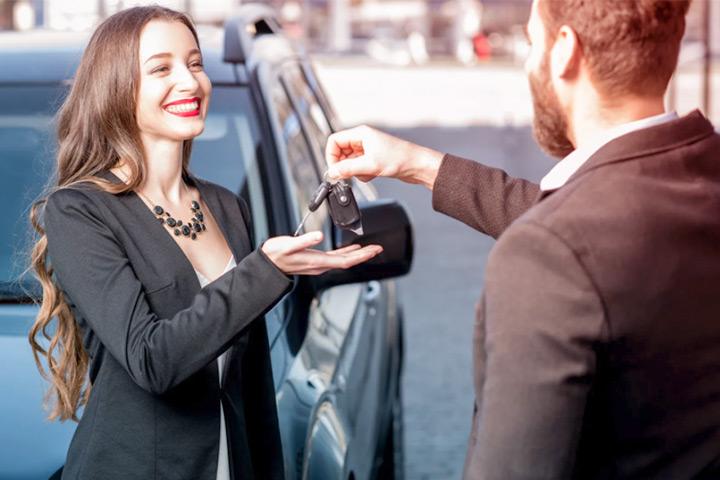 Jovem mulher recebendo as chaves do carro usado que acabou de comprar