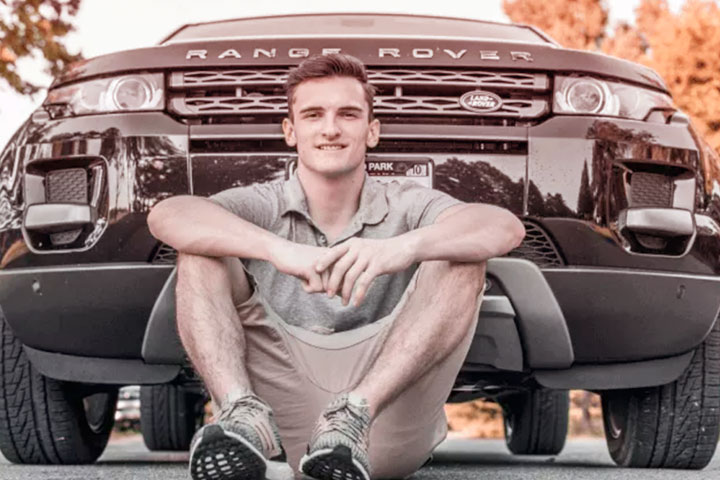 Jovem rapaz sorridente sentado no asfalto em frente a carro Range Rover