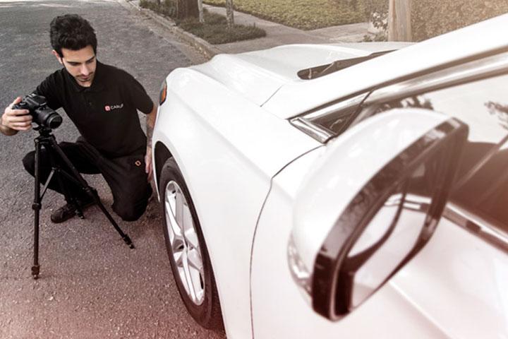 Fotógrafo da Carupi ajustando máquina fotográfica em tripé para fotografar carro usado para vender