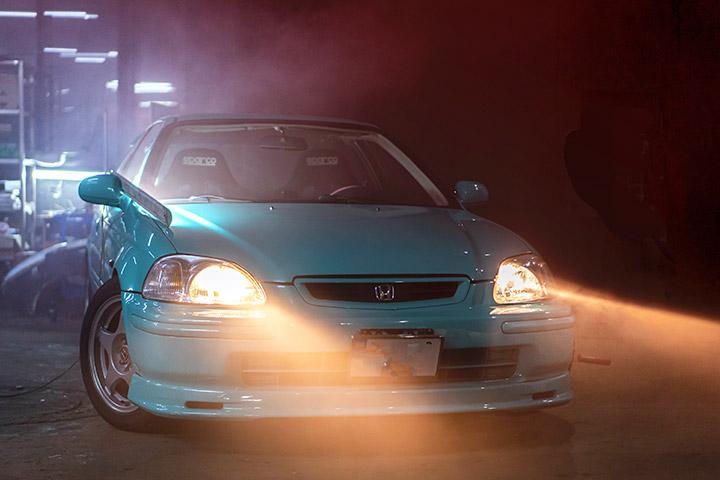 Frente de carro em cena noturna com faróis acesos e faixos de luz