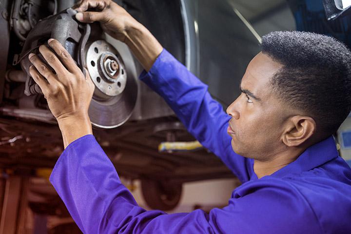 Mecânico com uniforme conferindo freio de carro erguido em elevador automotivo