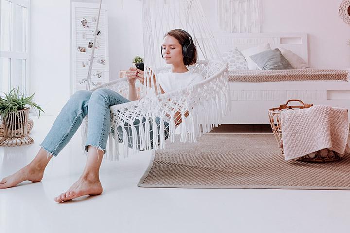 Jovem mulher relaxando na rede em sua sua casa e acessando aplicativo da Carupi para comprar carro online