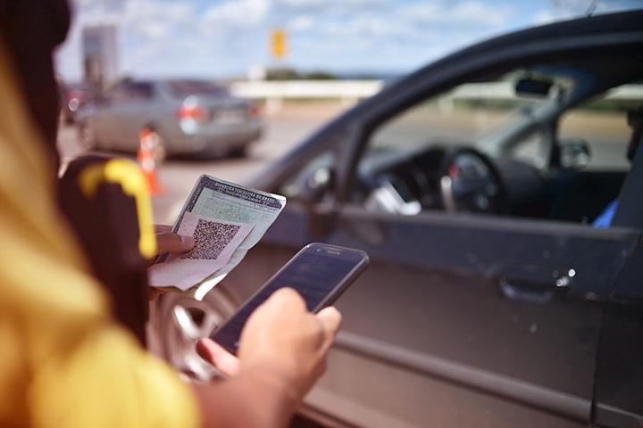 Close em agente de trânsito segurando CNH de motorista em uma mão e checando informações no celular com a outra