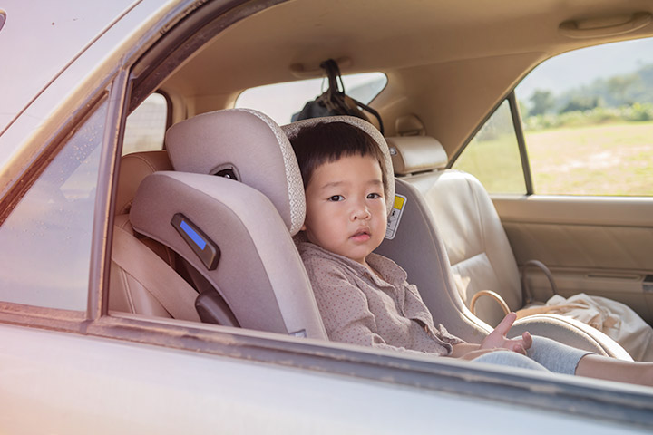 Criança oriental sentada em cadeirinha infantil no banco traseiro de carro olhando para fora pela janela