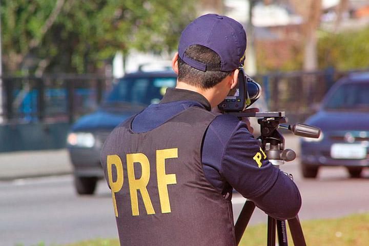 Policial Rodoviário Federal utilizando aparelho de radar de velocidade à beira de rodovia no Brasil