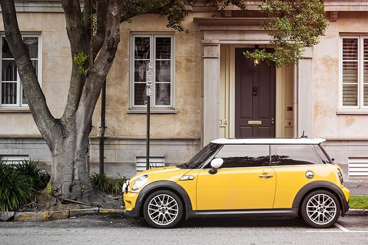 Mini Cooper amarelo estacionado em frente a casa antiga debaixo de árvore frondosa