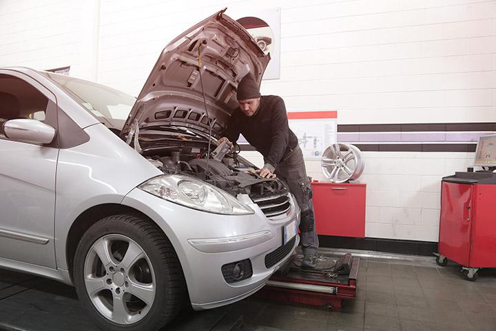 Carro prata em oficina mecânica de concessionária autorizada com capô aberto sendo inspecionado por mecânico
