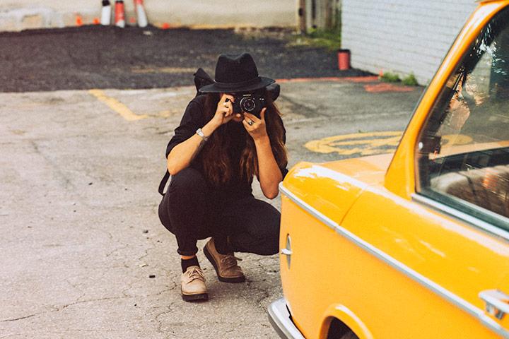Jovem mulher agachada com câmera fotográfica para fotografar carro antigo amarelo