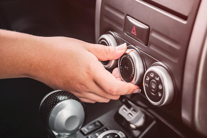 Destaque para mão regulando botão do ar condicionado em painel de instrumentos de carro