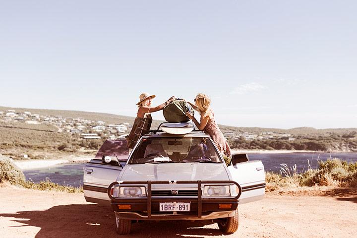 Duas mulheres colocando mala em bagageiro de teto de carro estacionado em paisagem mediterrânea