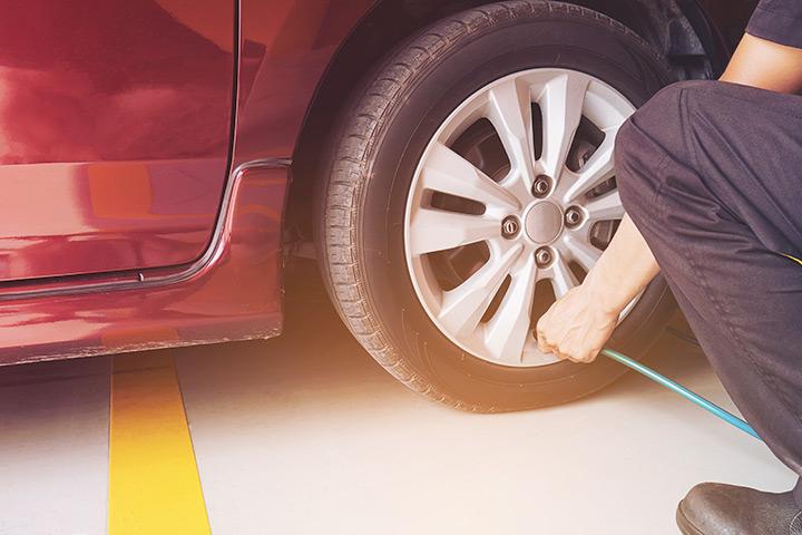 Destaque em pneu de carro sendo calibrado por homem segurando mangueira de ar