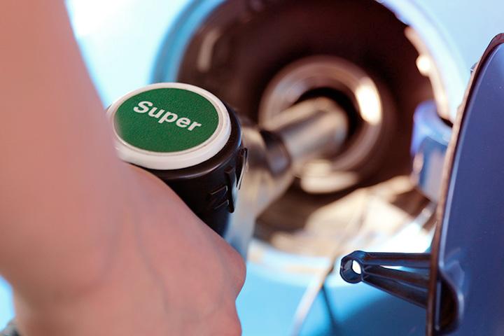 Close em mão segurando mangueira de combustível premium ao abastecer veículo