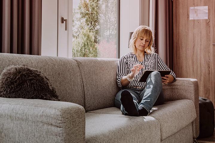 Mulher relaxando em sofá da sala enquanto acessa site da CARUPI em seu tablet