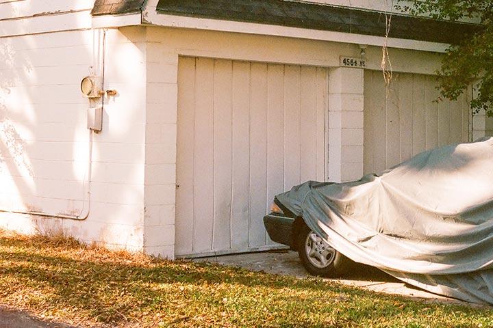Carro estacionado em frente a porta de garagem e coberto com lona para ficar parado por muito tempor