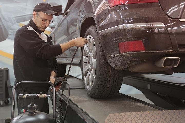 Homem calibrando pneu de carro em elevador automotivo de oficina mecânica