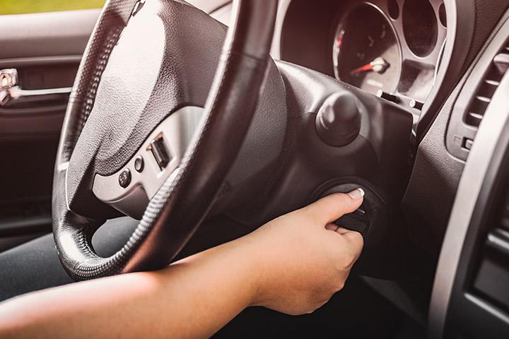 Mão de mulher girando chave de carro para dar partida no veículo que ficou parado por muito tempo