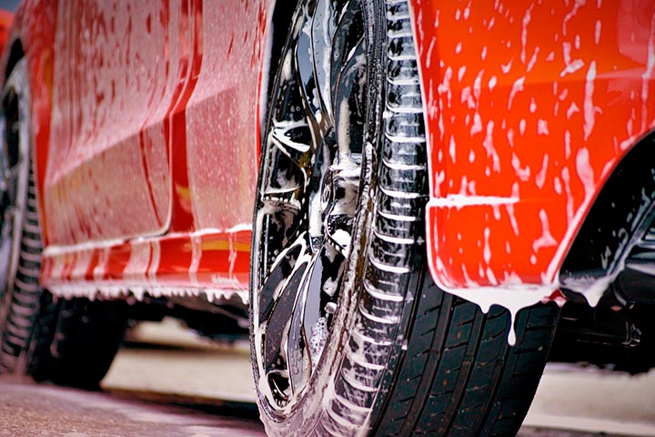 Close em rodas de carro vermelho sendo lavado, com espuma escorrendo pela carroceria