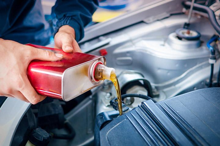 Mãos de homem segurando lata de óleo e despejando seu conteúdo em motor de carro