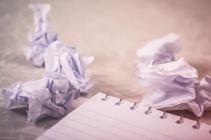 Folhas de papel amassadas com más ideias e caderno de anotações