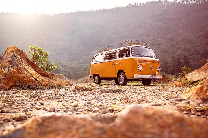 Volkswagen Kombi amarela antiga com bagageiros de teto estacionada em terreno pedregoso em cenário natural