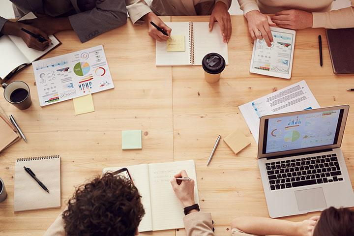 Mesa de trabalho de madeira em escritório com pessoas em reunião vista de cima