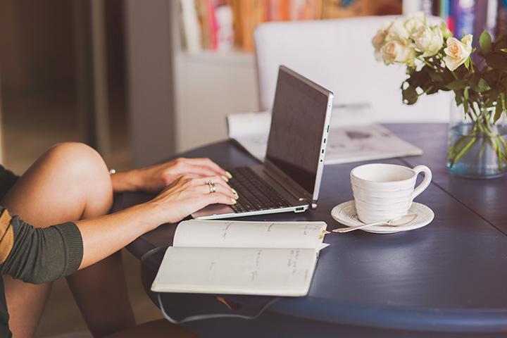 Jovem mulher em casa com notebook de mesa acessando website da CARUPI