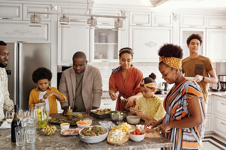 Família afro-americana com 7 membros de diferentes idades reunida ao redor de mesa da cozinha em momento descontraído