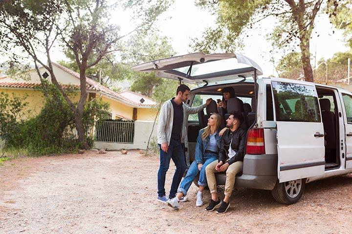 Jovens sentados no porta-malas de carro de 7 lugares conversando em frente a uma casa