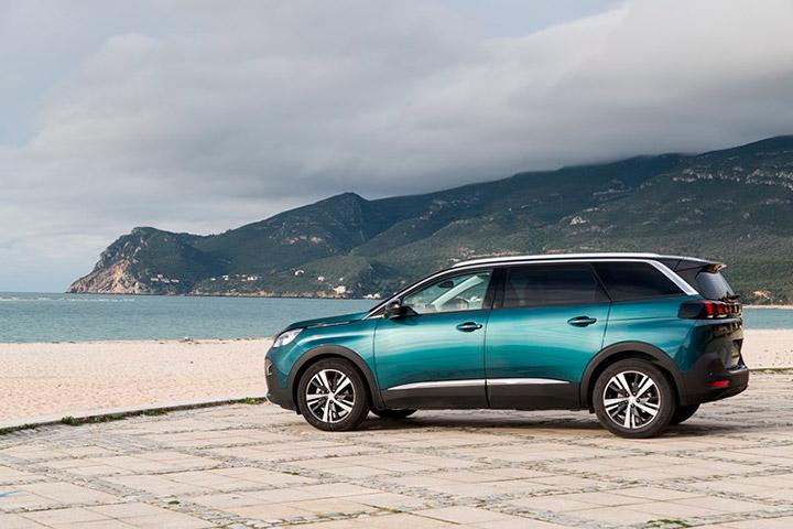 Carro de 7 lugares Peugeot 5008 em tom azulado estacionado em calçada em frente a praia com mar e montanhas ao fundo