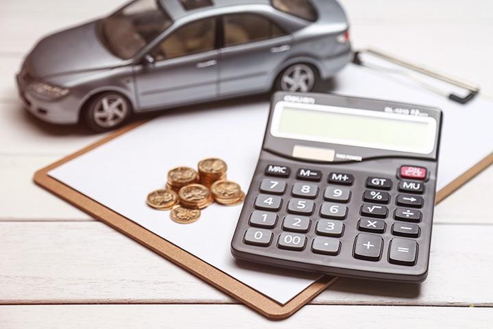Mesa com prancheta, calculadora, moedas e miniatura de um carro juntos