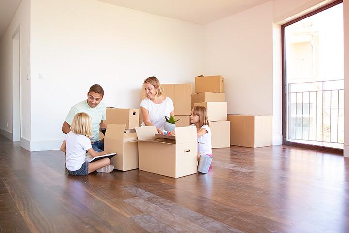 Família com pai, mãe e duas filhas em apartamento vazio ao lado de caixas de mudança