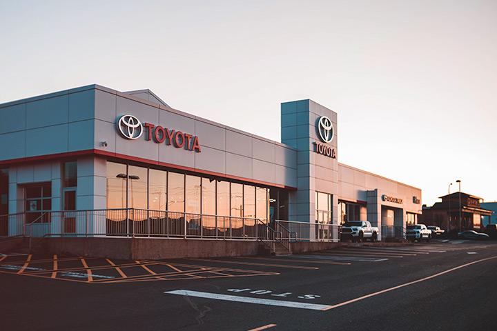 Fachada de concessionária Toyota ao entardecer com por-do-sol refletindo nos vidros