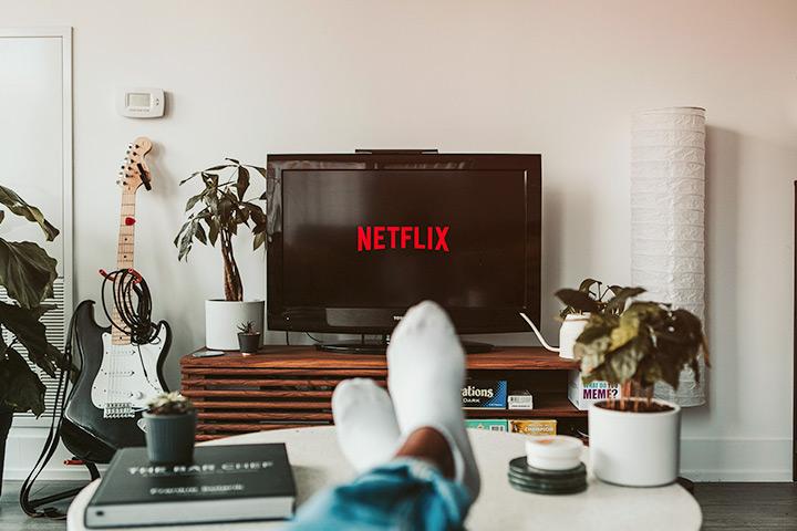 Vista do observador com pés apoiados sobre mesa de centro e televisor ligado na Netflix