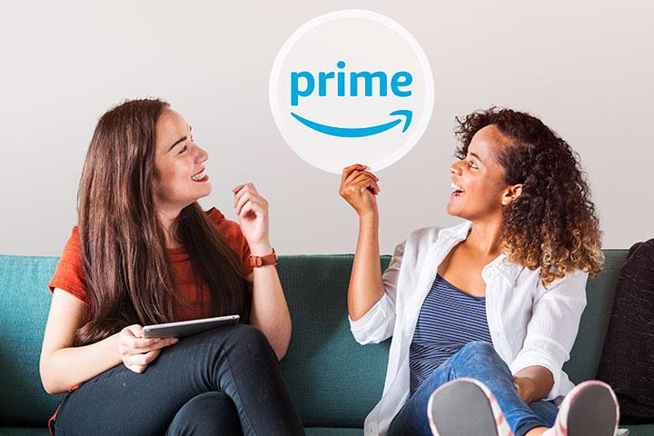 Duas jovens mulheres sentadas em sofá com tablet e segurando uma placa com logomarca da Amazon Prime