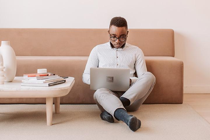 Jovem afro-americano sentado no tapete da sala de TV acessando website CARUPI em seu laptop