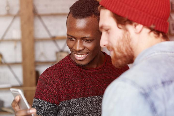 Homem Afro-americano mostrando tela de seu celular para amigo caucasiano e sorrindo