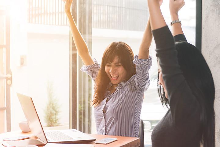 Jovens mulheres felizes e celebrando resultados com computador em mesa de trabalho