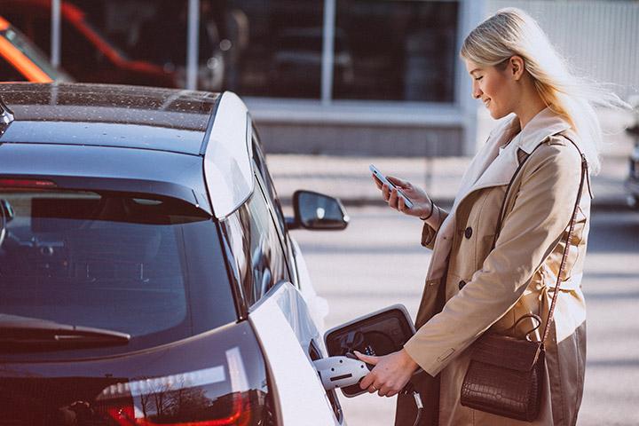 Jovem mulher carregando seu carro elétrico enquanto observa a tela de seu celular