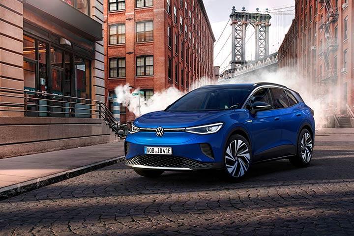 Carro elétrico ID.4 da Volkswagen na cor azul parado em rua de cidade industrial com prédios ao fundo