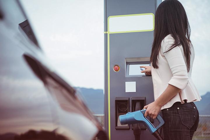 Jovem mulher segurando mangueira de carregamento de carro elétrico e configurando estação de carga