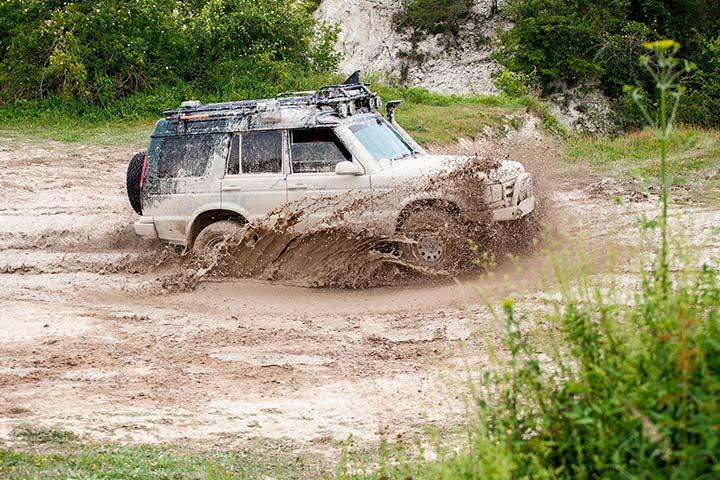 SUV 4x4 usado atravessando poça de lama em ambiente externo