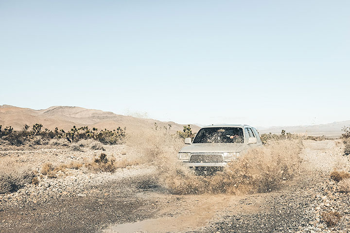 Carro SUV 4x4 cruzando poça de lama em cenário desértico