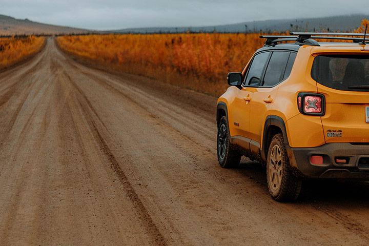 Jeep Renegade 4x4 amarelo em estrada rural com paisagem ao fundo