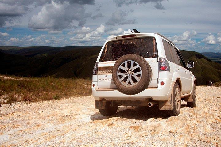 Mitsubishi Pajero TR4 branco em estrada rochosa no alto de montanha