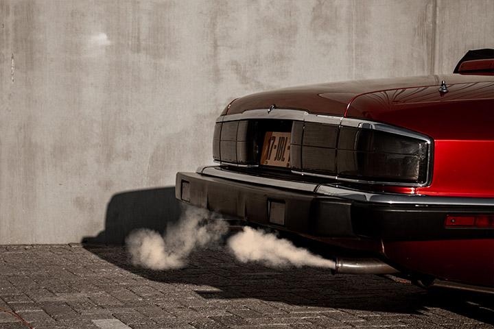 Traseira de carro sedã vermelho com escapamento soltando fumaça tóxica e poluente
