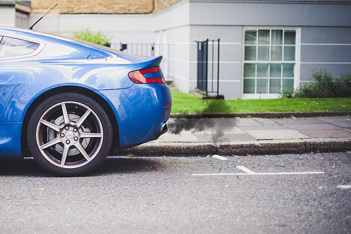 Traseira de carro esportivo azul estacionado em frente a uma casa soltando fumaça escura pelo escapamento