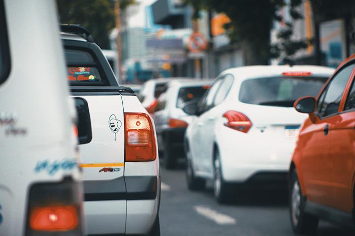Congestionamento em rua da cidade com diversos carros parados vistos por trás