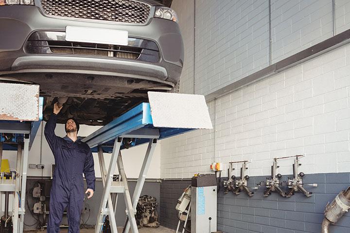 Mecânico trabalhando em parte inferior de carro levantado por elevador automotivo em oficina