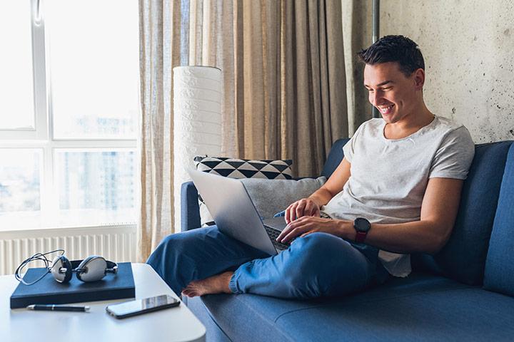 Rapaz sorridente em sofá de sua casa acessando website da Carupi para comprar carros usados online
